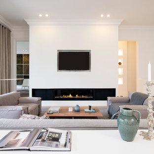ワシントンD.C.の北欧スタイルのおしゃれなLDK (白い壁、淡色無垢フローリング、横長型暖炉、壁掛け型テレビ) の写真