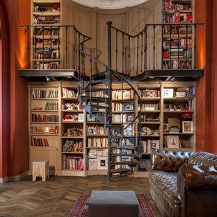 Ejemplo de biblioteca en casa clásica, sin chimenea, con parades naranjas, suelo de madera en tonos medios y suelo marrón