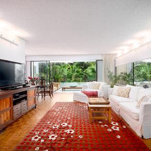 ハワイの中サイズのトロピカルスタイルのおしゃれなLDK (グレーの壁、無垢フローリング、暖炉なし、据え置き型テレビ、茶色い床) の写真