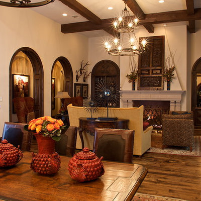 Living room - mediterranean open concept medium tone wood floor living room idea in Dallas with beige walls, a standard fireplace and a stone fireplace