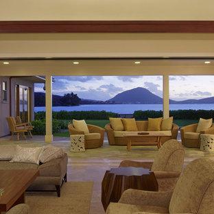 ハワイの大きいトロピカルスタイルのおしゃれなLDK (白い壁、トラバーチンの床、壁掛け型テレビ) の写真