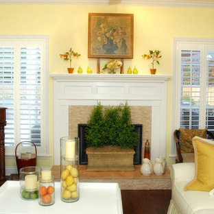 ジャクソンビルの中サイズのトランジショナルスタイルのおしゃれなLDK (黄色い壁、濃色無垢フローリング、標準型暖炉、石材の暖炉まわり、茶色い床) の写真