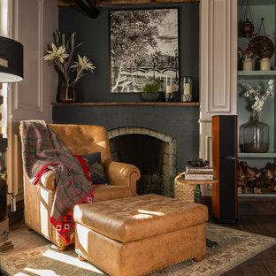 Cette image montre une salle de séjour traditionnelle avec une cheminée standard, un mur gris, un sol en bois foncé, un manteau de cheminée en brique et un sol marron.