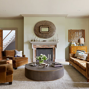 Example of a transitional light wood floor and beige floor living room design in New York with green walls, a standard fireplace and a brick fireplace