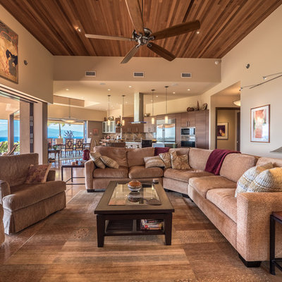 Large island style open concept limestone floor and beige floor living room photo in Hawaii with beige walls and a tv stand