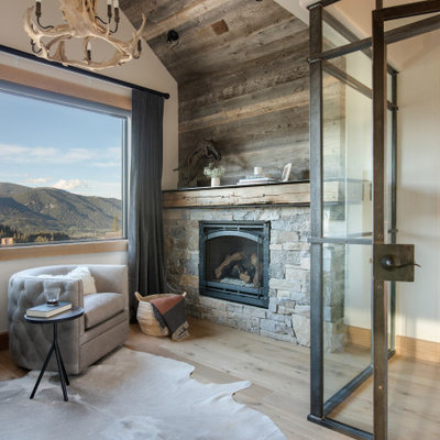 Example of a small mountain style loft-style light wood floor, brown floor and vaulted ceiling living room design in Other with white walls, a standard fireplace and a stone fireplace