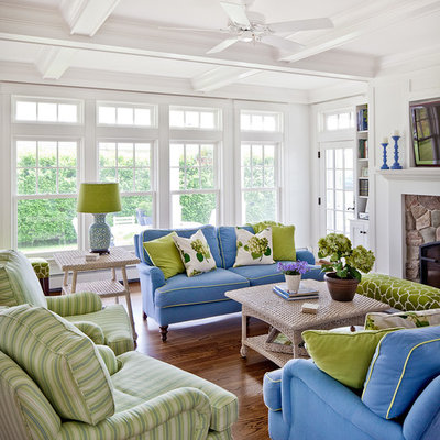 Example of a beach style enclosed medium tone wood floor and brown floor living room design in Portland Maine with white walls, a stone fireplace and a wall-mounted tv