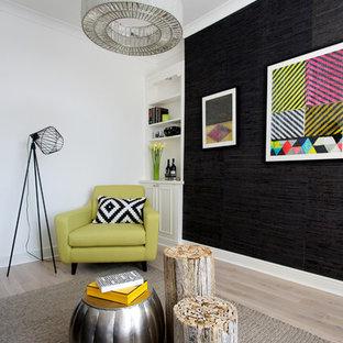 Bild på ett funkis vardagsrum, med svarta väggar och ljust trägolv