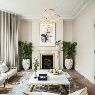 Design ideas for a medium sized traditional enclosed living room in London with beige walls, medium hardwood flooring, a standard fireplace and brown floors.