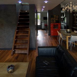 Esempio di un grande soggiorno contemporaneo stile loft con pareti grigie, parquet scuro, camino lineare Ribbon, cornice del camino in intonaco e parete attrezzata