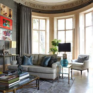 Esempio di un grande soggiorno classico stile loft con pareti grigie, pavimento in laminato, camino classico, cornice del camino in pietra e pavimento beige