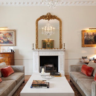 Example of a classic enclosed living room design in London with a standard fireplace