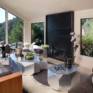 This is an example of a large world-inspired living room in San Francisco with beige walls and a metal fireplace surround.