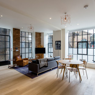 Design ideas for an urban open plan living room in London with white walls and light hardwood flooring.