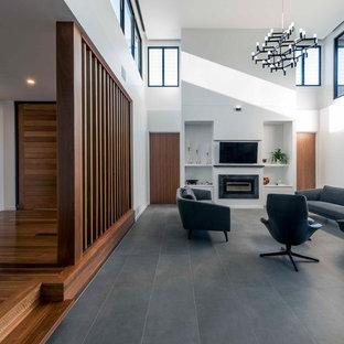 Inredning av ett modernt allrum med öppen planlösning, med vita väggar, klinkergolv i keramik, en standard öppen spis, en spiselkrans i trä, en väggmonterad TV och grått golv