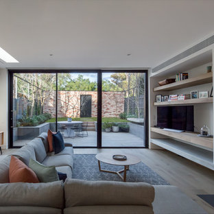 Contemporary living room in Melbourne with white walls, medium hardwood floors, a hanging fireplace and brown floor.