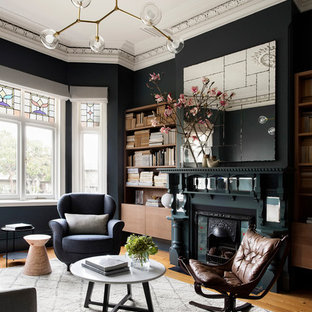 Transitional open concept living room in Melbourne with black walls, medium hardwood floors, a standard fireplace and brown floor.