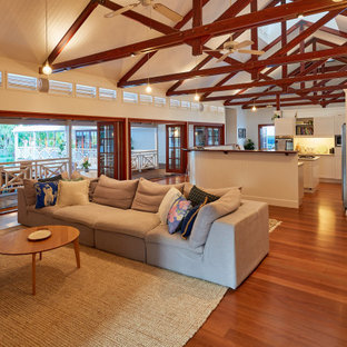 Inspiration for a tropical living room in Cairns with medium hardwood floors and exposed beam.
