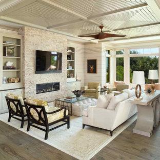 Idéer för att renovera ett maritimt vardagsrum, med vita väggar, mörkt trägolv, en bred öppen spis, en spiselkrans i sten och en väggmonterad TV