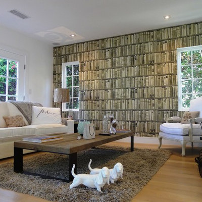 Example of a mid-sized eclectic enclosed light wood floor and beige floor living room library design in Los Angeles with a wall-mounted tv, beige walls and no fireplace
