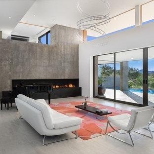 Foto de salón para visitas abierto, moderno, grande, sin televisor, con paredes blancas, chimenea lineal, marco de chimenea de hormigón, suelo de cemento y suelo gris