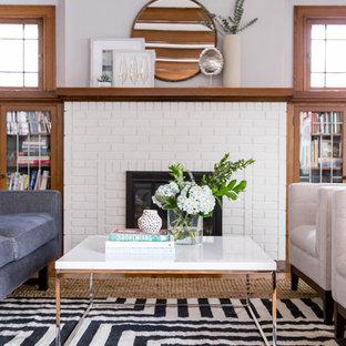 Foto de salón para visitas cerrado, retro, pequeño, sin televisor, con paredes blancas, suelo de madera clara, chimenea tradicional, marco de chimenea de ladrillo y suelo marrón