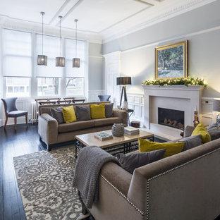 Immagine di un soggiorno tradizionale aperto e di medie dimensioni con sala formale, pareti grigie, pavimento in legno verniciato, camino classico e pavimento nero