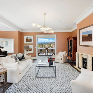 Design ideas for a transitional enclosed living room in Sydney with a library, orange walls, dark hardwood floors, a standard fireplace and brown floor.