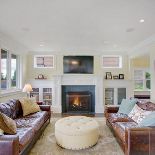 Inspiration for a craftsman living room remodel in Seattle with yellow walls, a standard fireplace and a wall-mounted tv
