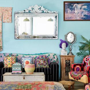 Ejemplo de salón abierto, bohemio, con paredes azules, suelo de cemento, estufa de leña y televisor independiente