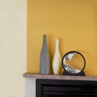 Идея дизайна: открытая гостиная комната среднего размера в стиле модернизм с желтыми стенами, полом из ламината, стандартным камином, фасадом камина из плитки и телевизором на стене