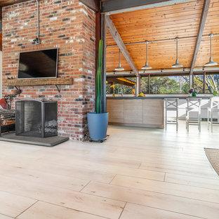 Imagen de salón abierto, minimalista, de tamaño medio, con suelo vinílico, paredes blancas, chimenea tradicional, marco de chimenea de ladrillo, televisor colgado en la pared y suelo beige