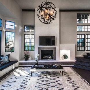 サンタバーバラの地中海スタイルのおしゃれなリビング (グレーの壁、濃色無垢フローリング、標準型暖炉、壁掛け型テレビ、タイルの暖炉まわり) の写真