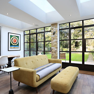 Medium sized contemporary enclosed living room in London with white walls, dark hardwood flooring, no fireplace, no tv and brown floors.