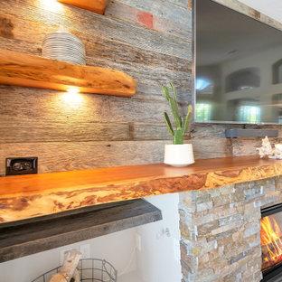 Esempio di un soggiorno di medie dimensioni e aperto con pareti grigie, pavimento in gres porcellanato, camino classico, cornice del camino in pietra ricostruita, TV a parete, pavimento grigio e pareti in legno