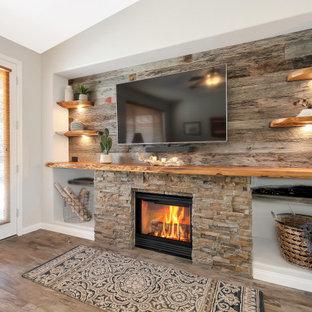 フェニックスの中くらいのおしゃれなLDK (グレーの壁、磁器タイルの床、標準型暖炉、積石の暖炉まわり、壁掛け型テレビ、グレーの床、板張り壁) の写真