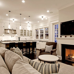 This is an example of a large traditional open concept living room in Seattle with white walls, a standard fireplace, a wall-mounted tv and dark hardwood floors.