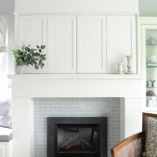 Imagen de salón abierto, costero, pequeño, con paredes grises, suelo de madera clara, chimenea tradicional, marco de chimenea de baldosas y/o azulejos, televisor retractable y suelo marrón