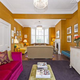 Imagen de salón abierto, actual, con parades naranjas, suelo de madera oscura, chimenea tradicional y televisor colgado en la pared