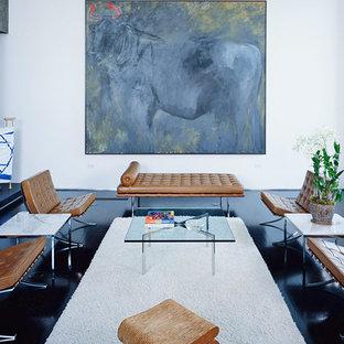 Immagine di un soggiorno minimalista stile loft con pareti grigie, parquet scuro, camino classico, cornice del camino in cemento e pavimento nero