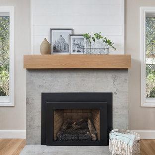 サンフランシスコのカントリー風おしゃれなリビング (グレーの壁、無垢フローリング、標準型暖炉、コンクリートの暖炉まわり、茶色い床) の写真