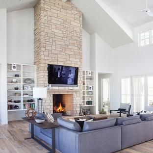 Exemple d'un salon nature ouvert avec un mur blanc, un sol en bois brun, une cheminée standard, un manteau de cheminée en pierre, un téléviseur fixé au mur et un sol marron.