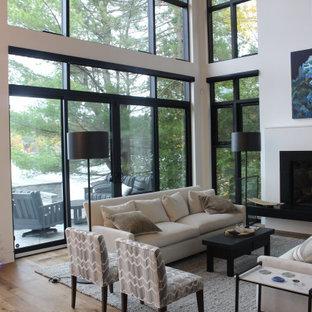 Esempio di un grande soggiorno design stile loft con pareti bianche, pavimento in laminato, camino sospeso, cornice del camino in pietra e pavimento marrone