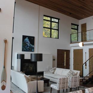 Ispirazione per un soggiorno design di medie dimensioni e aperto con sala formale, pareti bianche, pavimento in laminato, camino sospeso, cornice del camino in pietra, nessuna TV e pavimento marrone