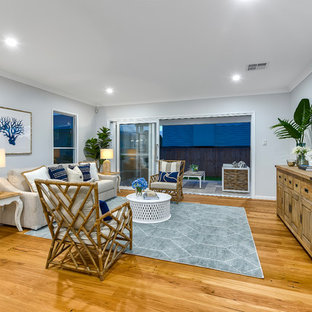 Photo of a beach style formal open plan living room in Brisbane with grey walls, medium hardwood flooring, no tv and brown floors.