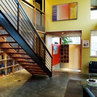 Imagen de salón abierto, urbano, pequeño, con paredes amarillas y suelo de cemento