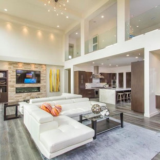 Inspiration for a contemporary open plan living room in San Diego with white walls, medium hardwood flooring, a ribbon fireplace, a stone fireplace surround, a wall mounted tv and grey floors.