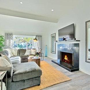 サンディエゴの大きいビーチスタイルのおしゃれなLDK (白い壁、セラミックタイルの床、標準型暖炉、石材の暖炉まわり、壁掛け型テレビ) の写真