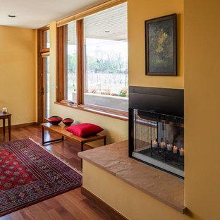 Idées déco pour un salon sud-ouest américain de taille moyenne et fermé avec un mur jaune, une salle de réception, un sol en bois clair, une cheminée d'angle, un manteau de cheminée en métal, aucun téléviseur et un sol beige.