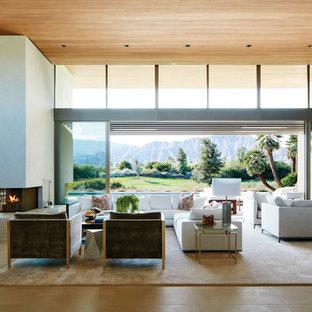 Ejemplo de salón con barra de bar abierto, moderno, grande, sin chimenea y televisor, con suelo de piedra caliza, marco de chimenea de yeso, paredes blancas y suelo beige